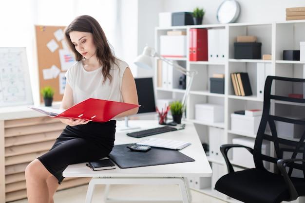 Ein junges mädchen setzte sich auf einen tisch im büro und hielt einen roten ordner in der hand.