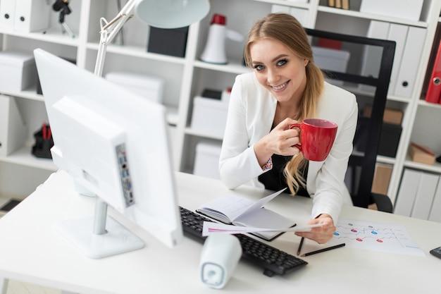 Ein junges mädchen sitzt am computertisch im büro und hält eine tasse und dokumente. vor dem mädchen sind die tabellen diagramme.