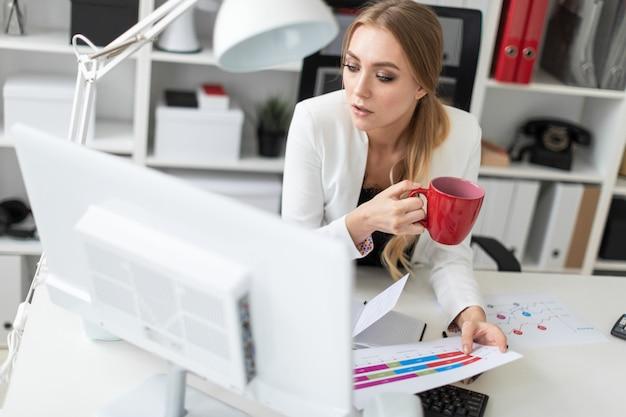 Ein junges mädchen sitzt am computertisch im büro und hält eine tasse und dokumente.