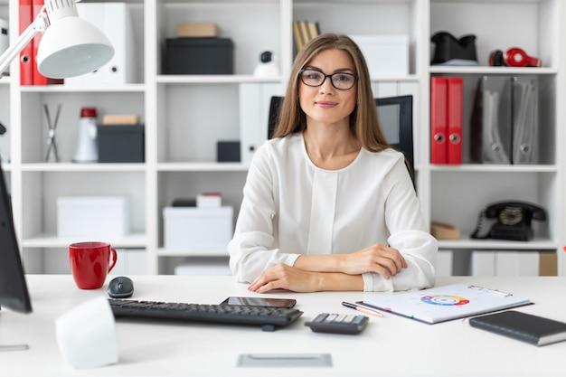 Ein junges mädchen sitzt am computertisch im büro.