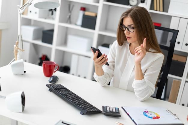 Ein junges mädchen sitzt am schreibtisch im büro und hält ein telefon in der hand.