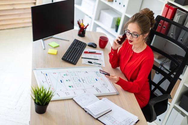Ein junges mädchen sitzt am schreibtisch im büro und hält eine bankkarte und ein telefon in der hand.