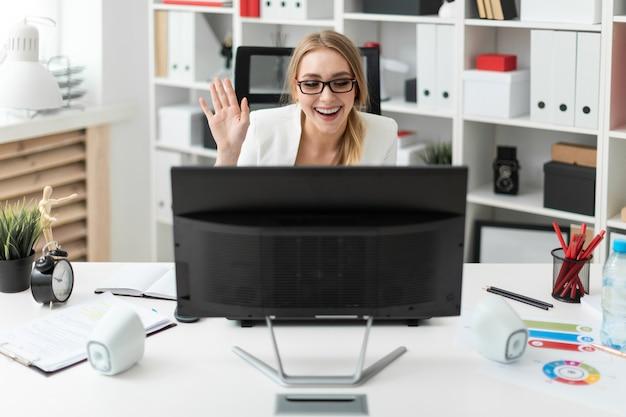Ein junges mädchen sitzt am tisch im büro, schaut auf den monitor und winkt mit der hand.