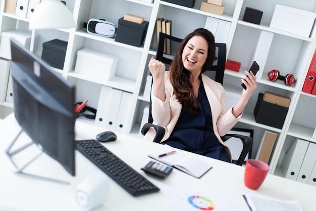 Ein junges mädchen sitzt an einem computertisch im büro und hält ein telefon in einer hand