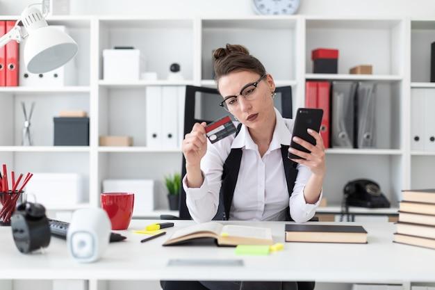 Ein junges mädchen sitzt an einem computertisch im büro und hält eine bankkarte und ein telefon.