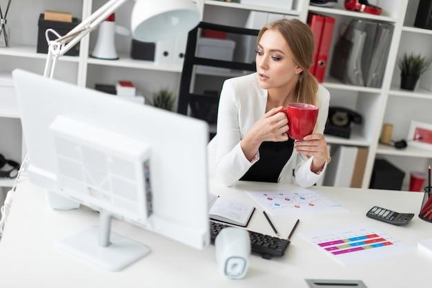Ein junges mädchen sitzt an einem computertisch im büro und hält eine rote tasse in der hand. vor dem mädchen auf dem tisch liegen diagramme.