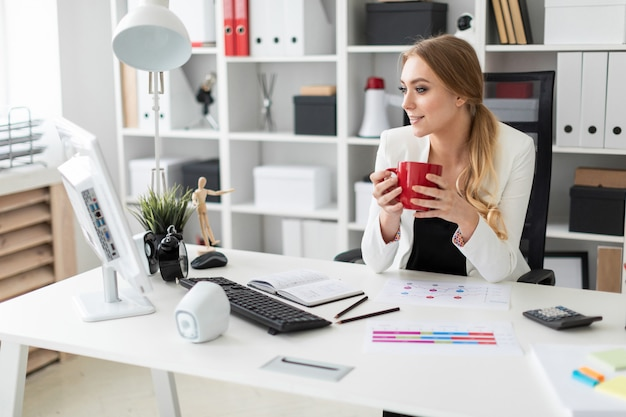 Ein junges mädchen sitzt an einem computertisch im büro und hält eine rote tasse in der hand.