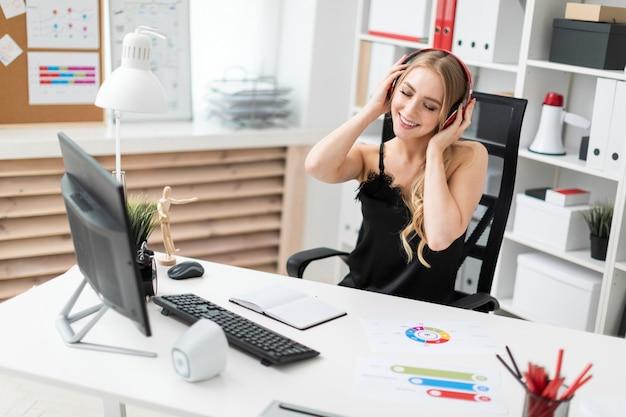 Ein junges mädchen sitzt an einem computertisch im büro und hört musik über kopfhörer.