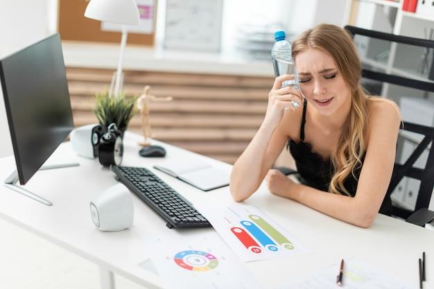 Ein junges mädchen sitzt an einem computertisch im büro und steckt sich eine flasche wasser an den kopf.