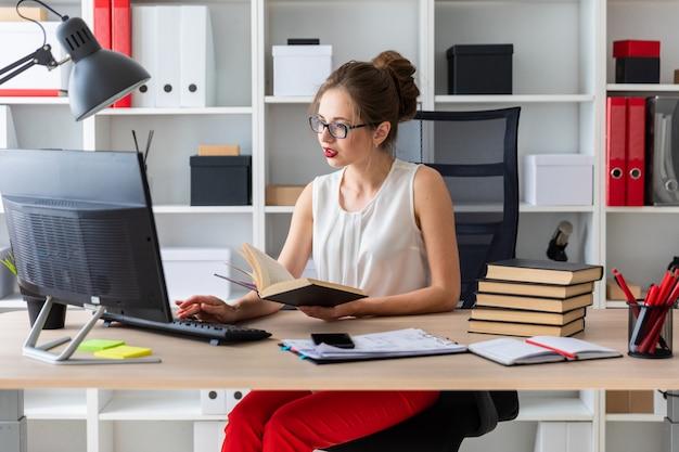 Ein junges mädchen sitzt an einem computertisch und hält ein offenes buch in den händen.