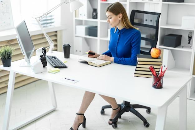 Ein junges mädchen sitzt an einem computertisch und hält eine gelbe markierung in der hand. vor dem mädchen liegt ein offenes buch.