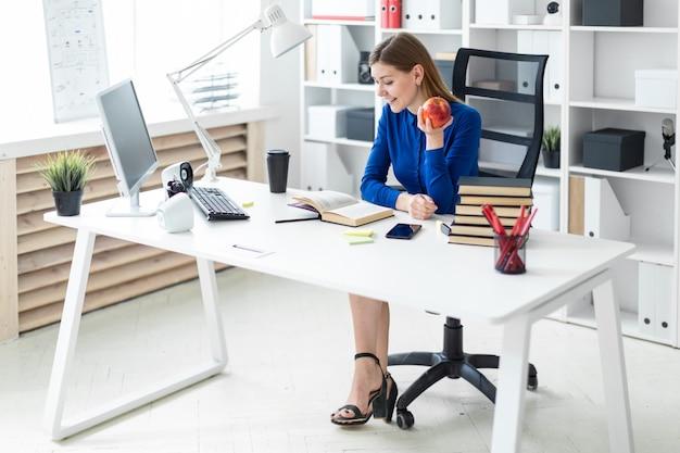Ein junges mädchen sitzt an einem computertisch und hält einen apfel in der hand. vor dem mädchen liegt ein offenes buch.
