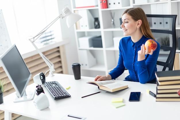 Ein junges mädchen sitzt an einem computertisch und hält einen apfel in der hand.