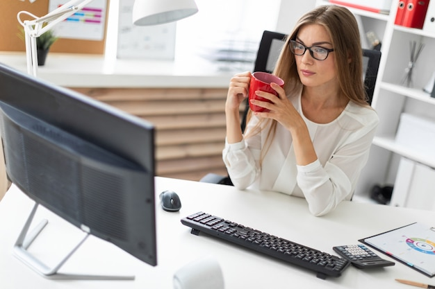 Ein junges mädchen sitzt an einem tisch im büro, hält eine rote tasse in der hand und schaut auf den monitor.