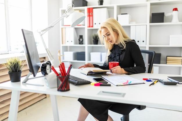 Ein junges mädchen sitzt an einem tisch im büro, hält eine tasse in der hand und liest ein buch.