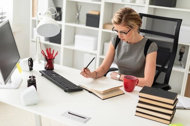 Ein junges mädchen sitzt an einem tisch im büro, hält einen bleistift in der hand und liest ein buch.