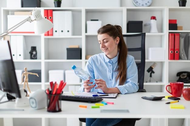 Ein junges mädchen sitzt an einem tisch im büro und hält eine flasche wasser in der hand.