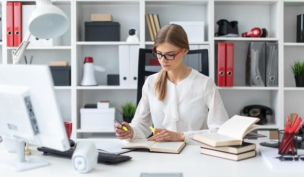 Ein junges mädchen sitzt an einem tisch im büro und hält eine gelbe markierung in der hand.