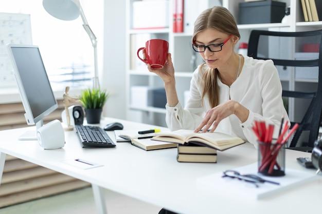 Ein junges mädchen sitzt an einem tisch im büro und hält eine rote tasse in der hand und liest ein buch.