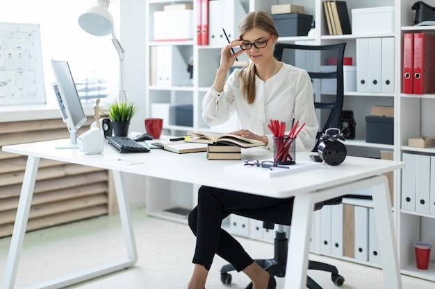 Ein junges mädchen sitzt an einem tisch im büro und hält einen bleistift in der hand. vor dem mädchen liegt ein offenes buch.