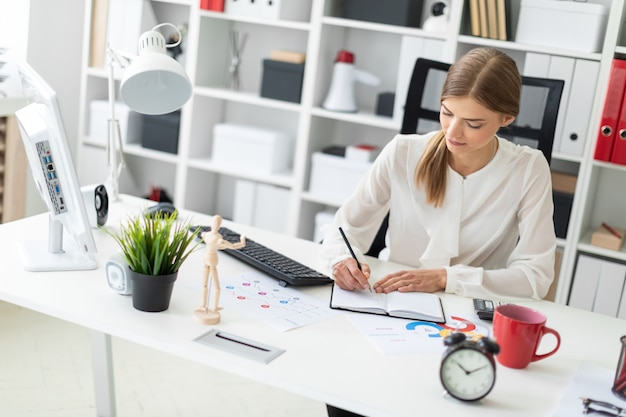 Ein junges mädchen sitzt an einem tisch im büro und schreibt mit einem bleistift in ein notizbuch.