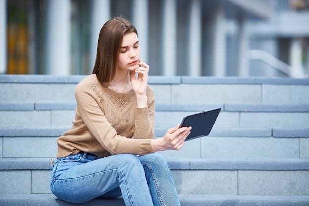 Ein junges mädchen sitzt auf der treppe und schaut auf das tablett.