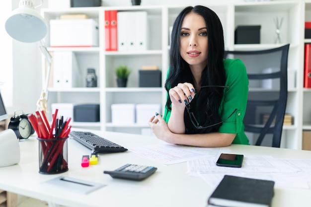 Ein junges mädchen sitzt im büro am tisch und hält eine brille in den händen.