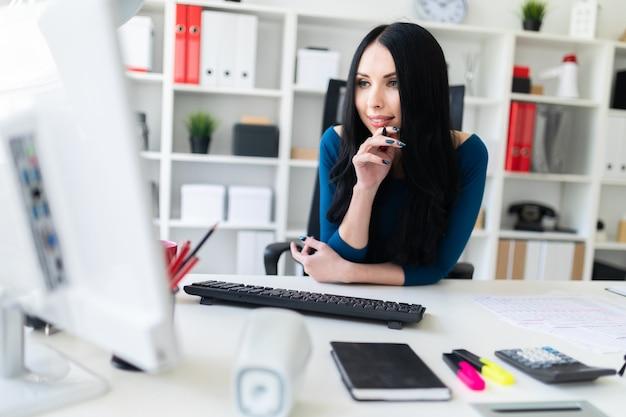 Ein junges mädchen sitzt im büro an einem tisch, schaut auf den monitor und hält einen stift in der hand.