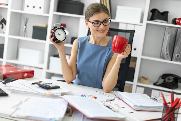 Ein junges mädchen sitzt in ihrem büro an einem tisch und hält einen wecker und eine rote tasse in der hand.