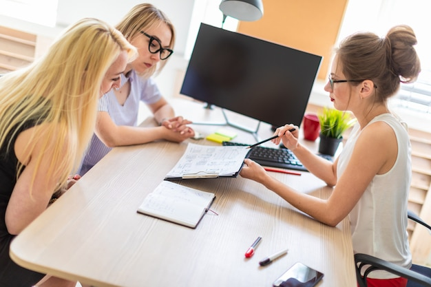Ein junges mädchen sitzt in ihrem büro an einem tisch und spricht mit zwei mitgesellschaftern.