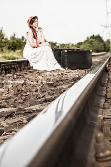 Ein junges mädchen sitzt mit einem koffer auf den eisenbahnschienen.