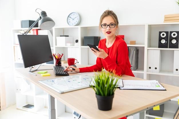 Ein junges mädchen steht an einem tisch im büro und hält eine schwarze markierung und ein telefon in der hand.