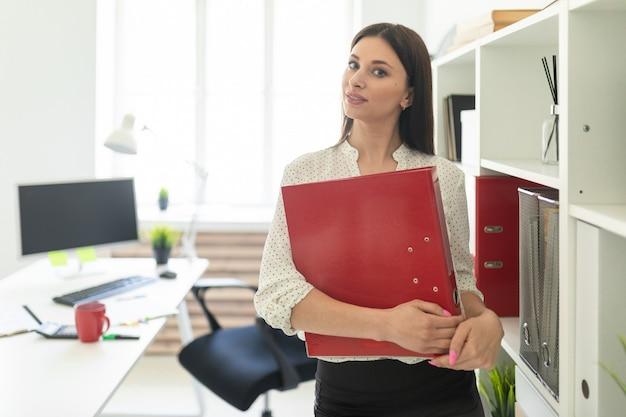 Ein junges mädchen steht im büro in der nähe des tisches und hält einen ordner mit dokumenten.