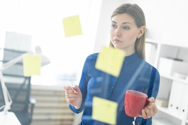 Ein junges mädchen steht im büro in der nähe eines transparenten brettes mit aufklebern und hält eine rote tasse in den händen.