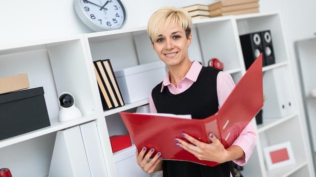 Ein junges mädchen steht im büro mit einem roten ordner in den händen.