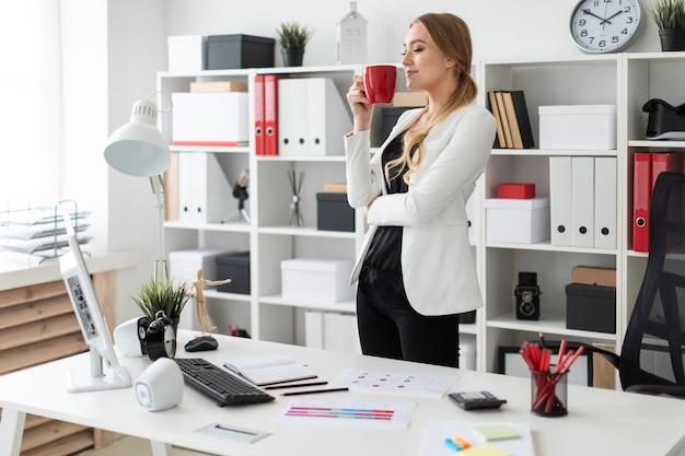 Ein junges mädchen steht im büro nahe einem computertisch und hält eine rote schale in ihren händen