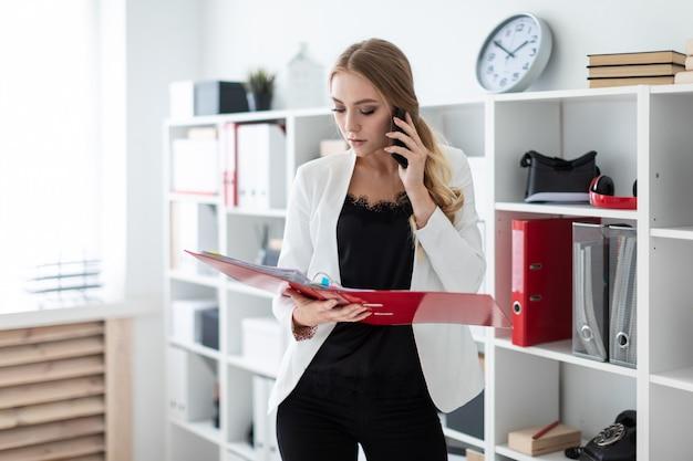 Ein junges mädchen steht im büro neben dem regal, telefoniert und hält einen ordner in der hand