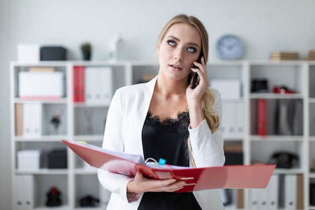Ein junges mädchen steht im büro neben dem regal, telefoniert und hält einen ordner mit dokumenten in der hand.