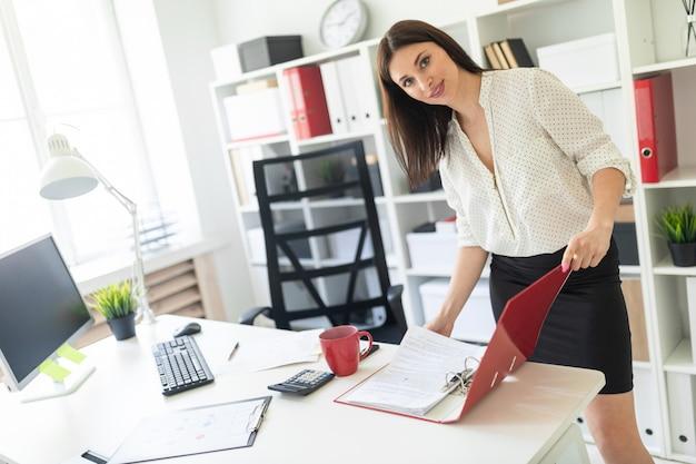 Ein junges mädchen steht im büro neben dem tisch und blättert in der mappe mit den dokumenten.