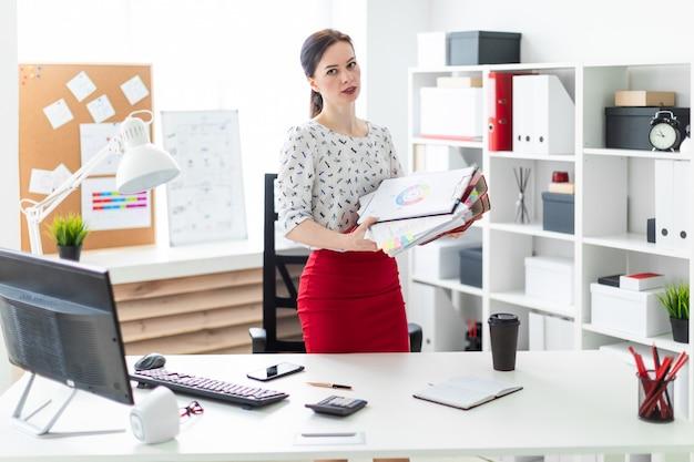 Ein junges mädchen steht in der nähe eines computertisches im büro und hält ordner und grafiken.
