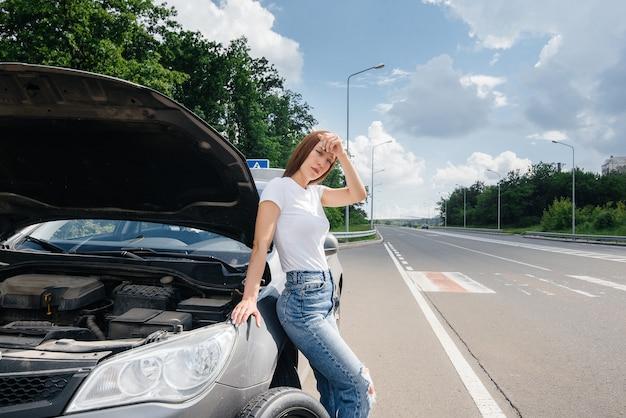 Ein junges mädchen steht in der nähe eines kaputten autos mit einem kaputten rad mitten auf der autobahn und wartet frustriert an einem heißen tag auf hilfe. panne und panne des autos. warten auf hilfe.