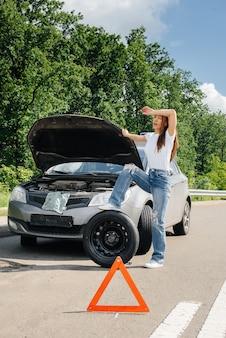 Ein junges mädchen steht in der nähe eines kaputten autos mitten auf der autobahn und versucht an einem heißen sonnigen tag ein kaputtes rad zu wechseln. ausfall und panne des autos. warten auf hilfe.