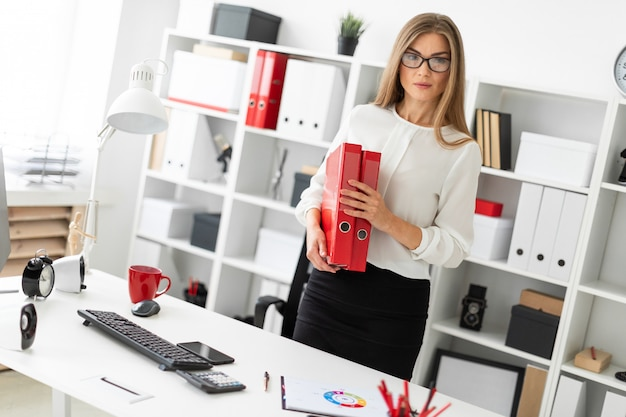 Ein junges mädchen steht in der nähe eines tisches im büro und hält einen ordner mit dokumenten.
