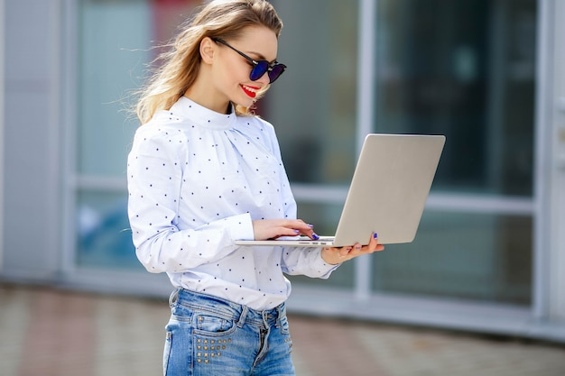 Ein junges mädchen steht mit einem laptop in der hand auf der straße. setzen sie auf das mädchen eine sonnenbrille.