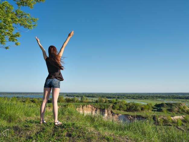 Ein junges mädchen steht mit erhobenen armen zum himmel. entspannte junge frau mit blick in die aussicht. friedliches mädchen, das an einer klippe steht und die landschaft genießt. - im freien. porträt in voller länge