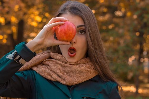 Ein junges mädchen steht mit offenem mund im park und hält apple in der nähe der augen