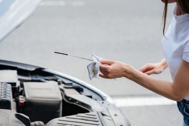 Ein junges mädchen steht mitten auf der autobahn neben einem kaputten auto und kontrolliert den ölstand im motor. ausfall und panne des autos. warten auf hilfe.