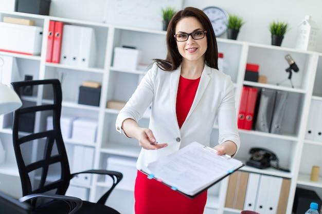 Ein junges mädchen steht neben einem schreibtisch im büro und streckt einen stift und ein dokument aus.