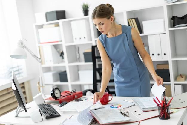 Ein junges mädchen steht neben einem tisch im büro und blättert durch die dokumente.
