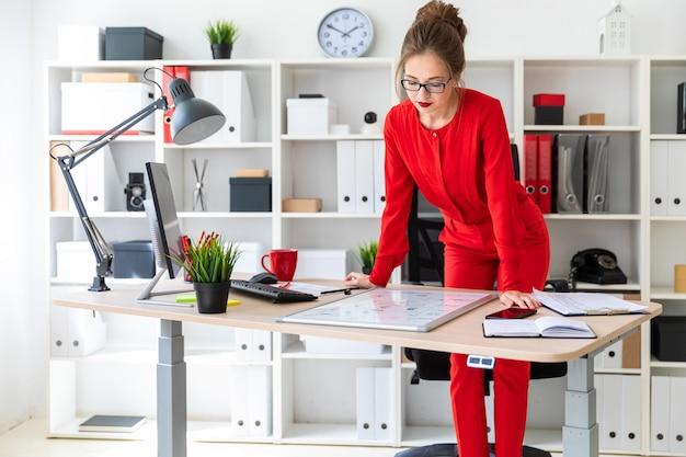 Ein junges mädchen steht neben einem tisch in ihrem büro, hält einen marker in der hand und schaut auf die magnettafel.